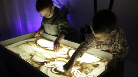 hildren draw with their hands on the sand with illumination Stock Footage