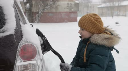 süpürge : Little boy outdoors cleaning a snowy car in winter morning.