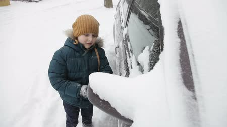 Little boy outdoors cleaning a snowy car in winter morning.