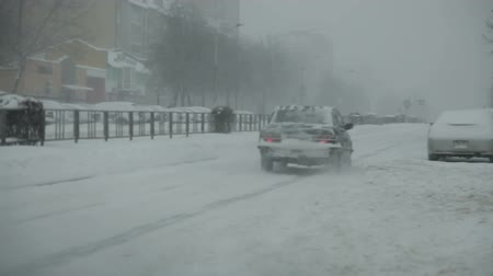 Snow-covered city road with cars in the snow