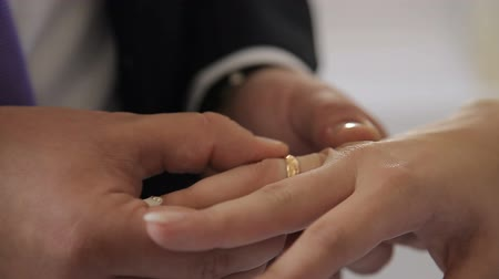 The groom wears a ring to the bride