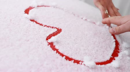A loving couple draw a heart in the snow Stock Footage