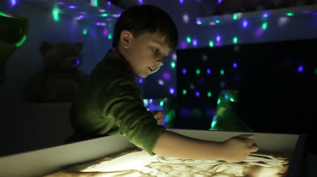 hildren draw with their hands on the sand with illumination Стоковые видеозаписи