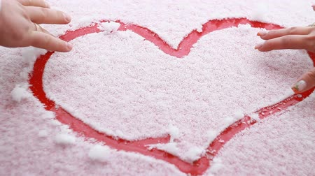 sfondo romantico : A loving couple draw a heart in the snow Filmati Stock