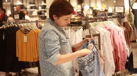 seçme : The girl chooses clothes in the store