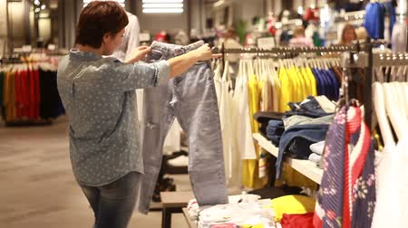 decisões : The girl chooses clothes in the store