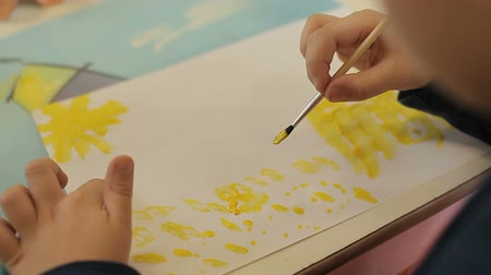 щеткой : The boy draws yellow paints on a piece of paper