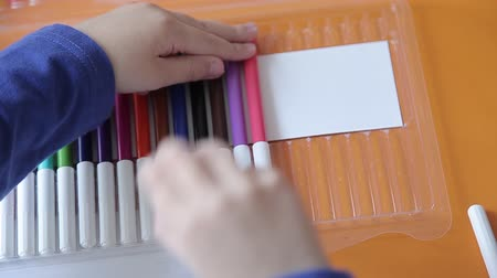 рекламный : The boy folds colored markers