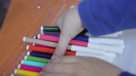 basit : The boy takes colored markers for drawing Stok Video