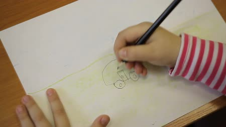 kotki : A boy draws a car with a pencil Wideo