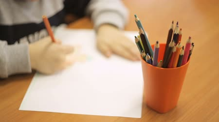 иероглиф : A boy draws a drawing with colored pencils