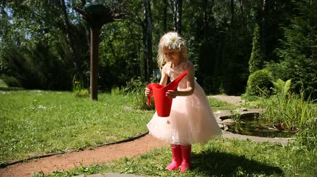 działka : Little girl takes a red watering can