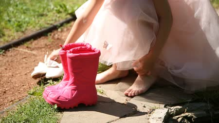 adil : Little girl puts on rubber boots Stok Video