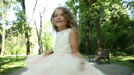 green grass : Little girl in dress having fun in park Stock Footage