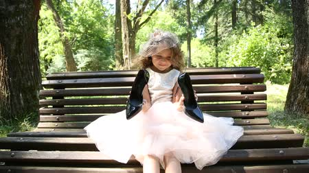 maternidade : Little girl on the bench holding big shoes