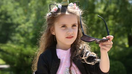 happiness symbol : Little girl takes off sunglasses