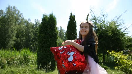 kotki : Little girl is playing with a red pillow Wideo