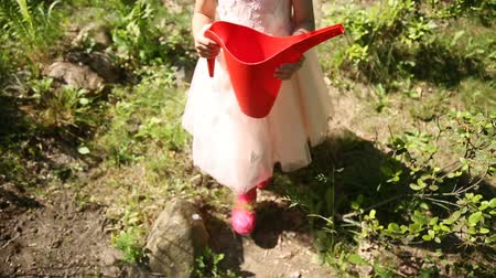 konewka : Little girl with red watering can Wideo