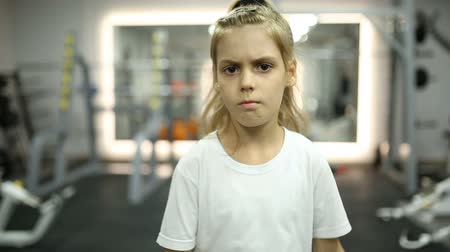 тренер : A little girl is lifting dumbbells in a gym