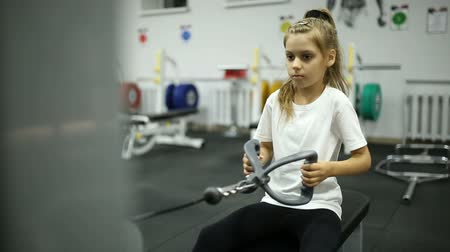 жесткий : A little girl in the gym is exercising on the machine Стоковые видеозаписи