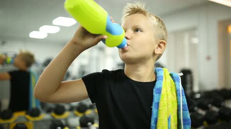 towel white : The boy at the gym is drinking water
