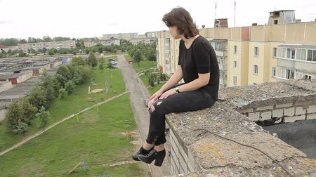 riskli : Teen girl sitting on the edge of the roof
