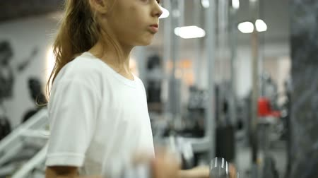 жесткий : Little girl in the gym engaged with dumbbells Стоковые видеозаписи