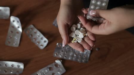 glied : A teenager girl takes out the pills from the package
