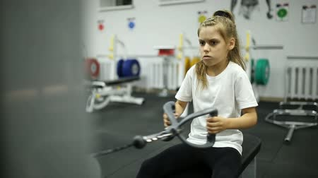 engaged : The child in the gym is exercising on the simulator