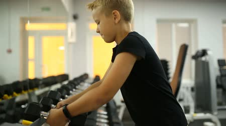 abuse : The boy chooses a dumbbell Stock Footage
