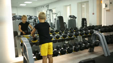 жесткий : The boy is training dumbbells Стоковые видеозаписи