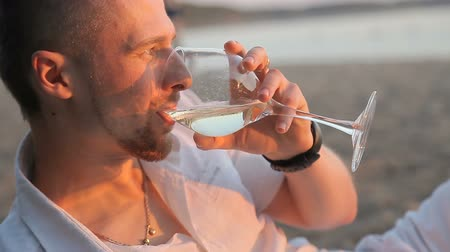 чувствовать : Guy drinks wine with a glass on the beach