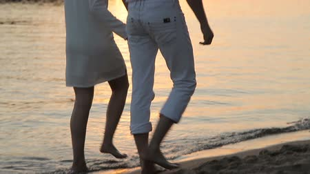 suntan : A guy and a girl are walking along the beach at sunset