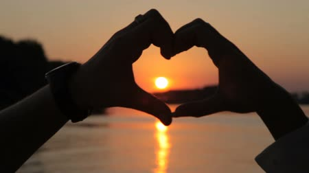 příloha : Symbol of love, heart from the hands of lovers at sunset