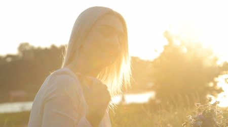 harmonie : Blonde girl at sunset collects flowers