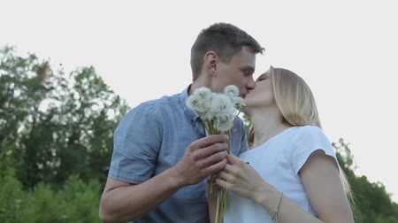 engaged : The guy and the girl blow on dandelions
