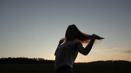 легкий : Girl touches her hair at sunset