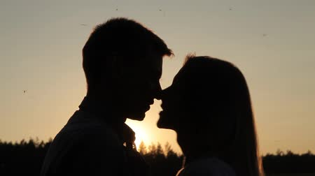 закрытыми глазами : the guy and the girl are kissing at sunset
