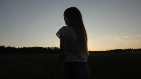 osamělost : the girl is walking in the field at sunset Dostupné videozáznamy
