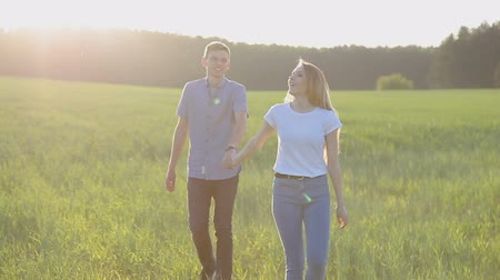 rear : A guy and a girl are walking on the grass, holding hands