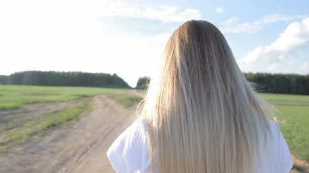 alto : Blonde girl walking on a field road