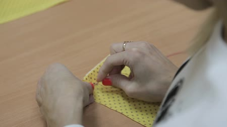 têxteis : The girl sews by hand a needle and a red thread Stock Footage