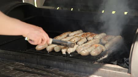 kiełbasa : Man roasts sausages on the grill