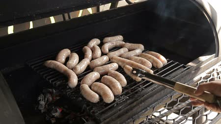 kiełbasa : A man puts sausages on the barbecue for frying