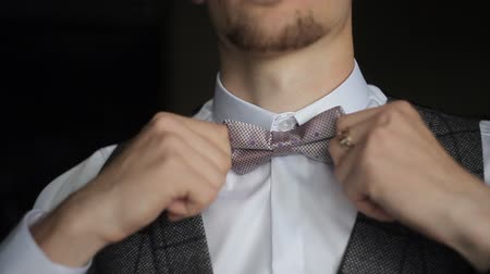 especial : The groom straightens a bow tie