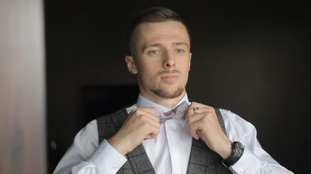 ajustando : A man dresses and straightens a bow tie