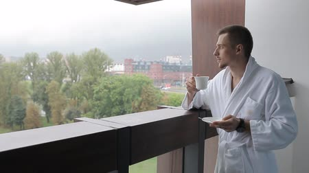 sudeste : A young man in a bathrobe is drinking coffee on the balcony