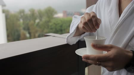grãos de café : A man in a bathrobe is stirring coffee with a spoon Vídeos