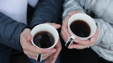 恋人 : Cups of coffee in the hands of a girl and a guy lovers drink coffee.
