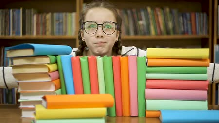 vybírání : The girl in glasses in the library hugs books. Dostupné videozáznamy